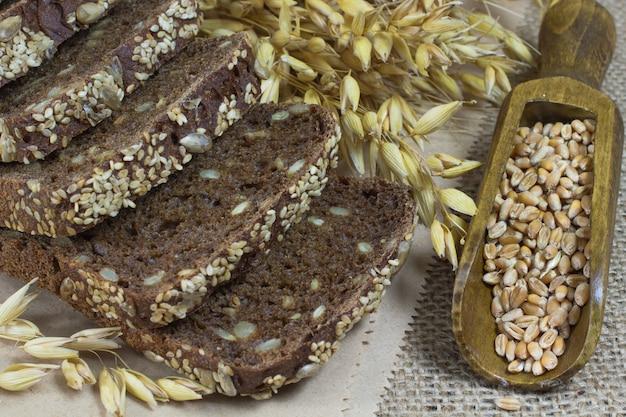 Pão preto com sementes de gergelim e sementes de girassol, espigas de aveia e grãos de trigo em uma colher de pau