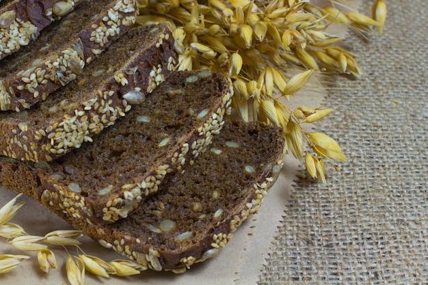 Pão preto com sementes de gergelim e sementes de girassol, espigas de trigo na sacaria