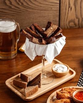 Pão preto de frente com molho e frango na mesa de madeira marrom