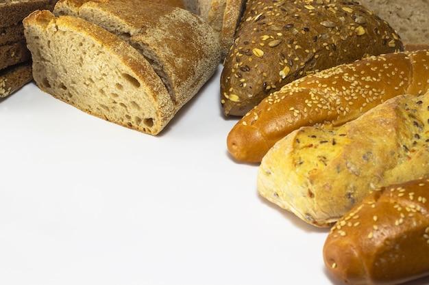 Pão preto e branco com sementes de girassol e baguetes de gergelim em uma superfície branca