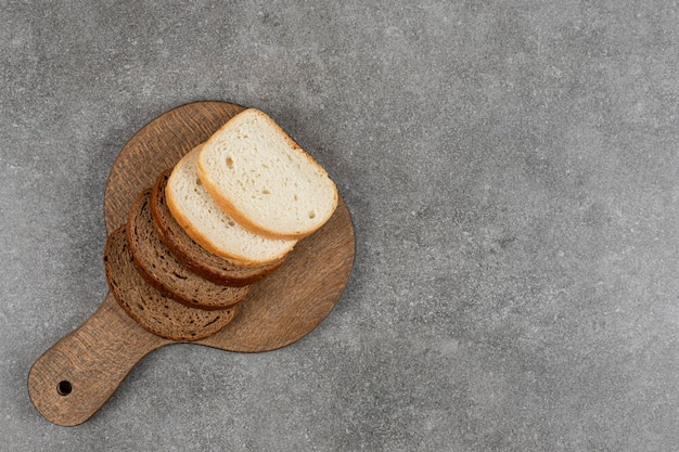 Pão preto e branco fatiado em tábua de madeira