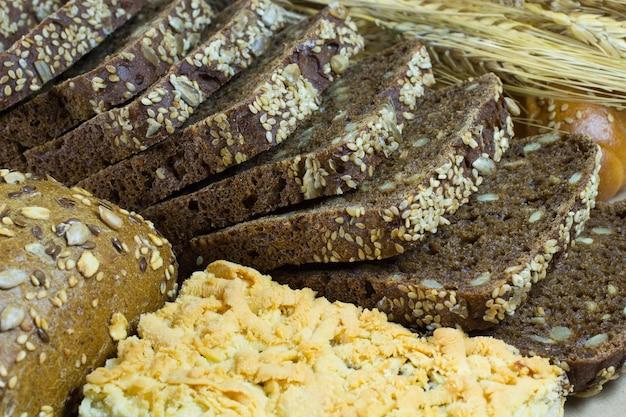 Pão preto fatiado com gergelim e sementes de girassol, pão branco