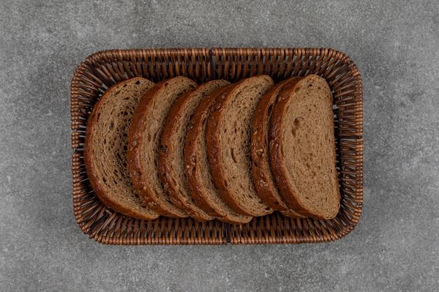 Pão preto fatiado em cesta de madeira