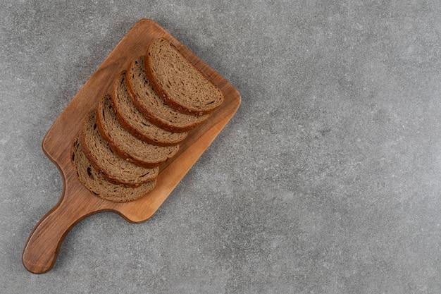 Pão preto fatiado em tábua de madeira