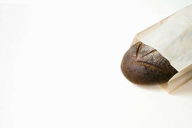 Pão preto fresco em um saco de papel em um fundo branco. copie o espaço. padaria cozimento fresco