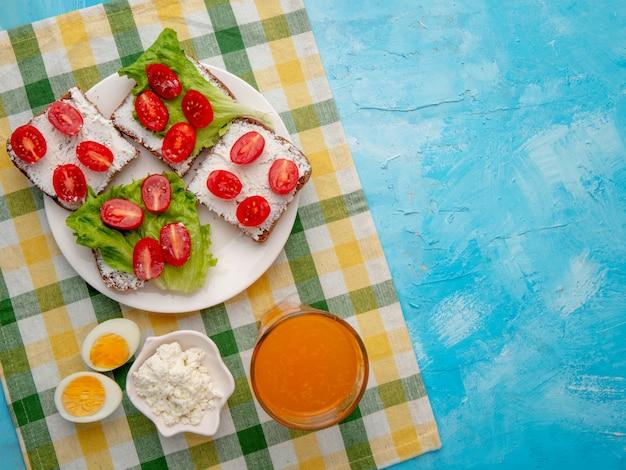 Pão queijo ovo e suco de laranja na mesa azul