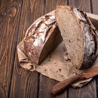 Pão quente fresco cortado ao meio em uma velha mesa de madeira com uma faca