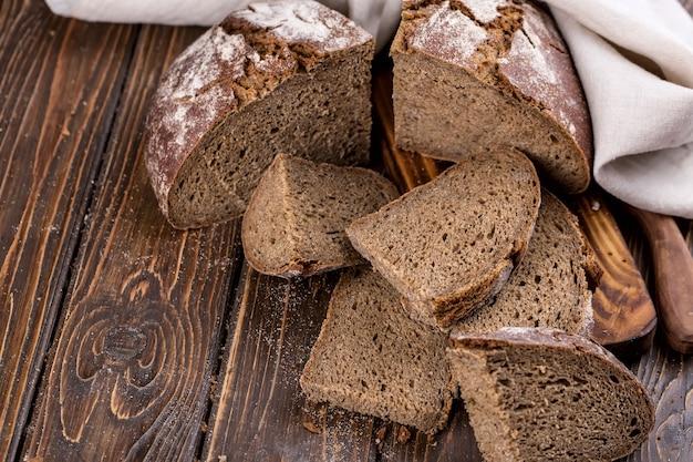 Pão quente fresco cortado em pedaços em uma velha mesa de madeira, com guardanapo