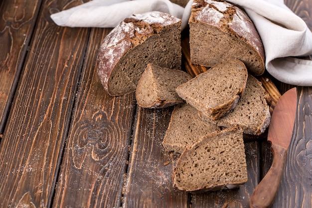 Pão quente fresco cortado em pedaços em uma velha tábua de madeira, horizontal