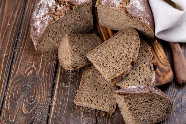 Pão quente fresco cortado em pedaços em uma velha tábua de madeira