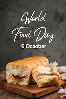 Pão rasgado recheado com fio dental e maionese em uma mesa de madeira com a inscrição dia mundial da alimentação