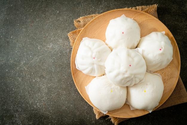Pão recheado no vapor em prato de madeira - comida chinesa
