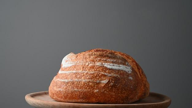 Pão redondo assado em bandeja de madeira