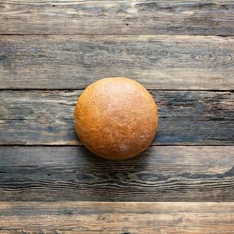 Pão redondo de pão cinza com fundo de madeira close-up