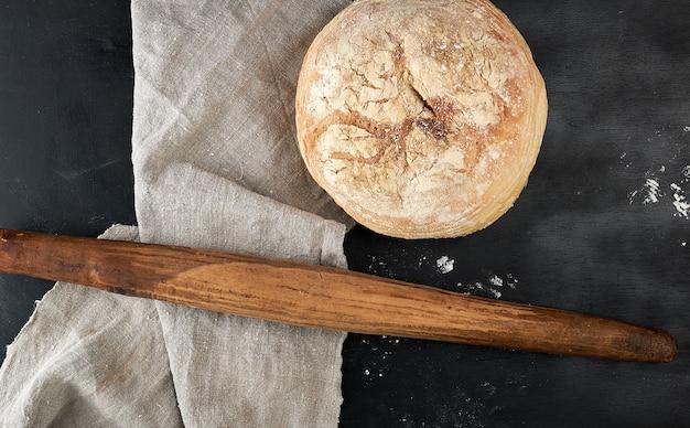 Pão redondo e velho rolo de madeira sobre uma mesa preta