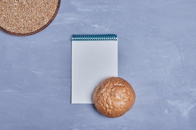 Pão redondo feito à mão com um livro de receitas à parte.