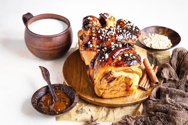 Pão retorcido de geleia de damasco ou babka com nozes e especiarias com um copo de leite. babka de pão de fermento caseiro.