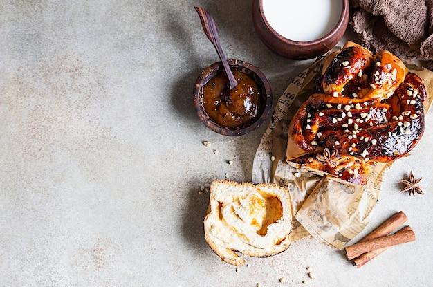 Pão retorcido de geleia de damasco ou babka com nozes e especiarias com um copo de leite.