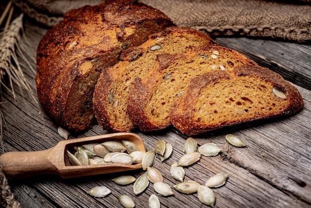 Pão rústico com abóbora e sementes de abóbora em uma velha mesa de madeira.