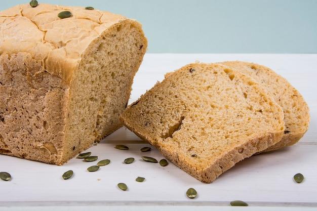 Pão rústico de fermento de trigo com sementes de abóbora na superfície da placa de madeira branca studio photo