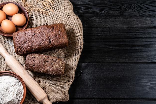 Pão rústico e trigo na mesa de madeira escura. fundo escuro temperamental com espaço de texto livre.