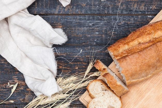 Pão rústico na mesa de madeira com trigo e pano