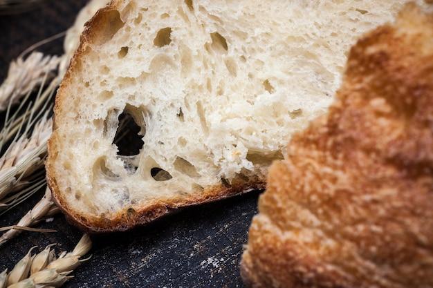 Pão rústico na mesa de madeira. fundo de madeira escuro