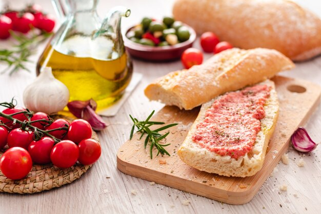 Pão rústico, tomate e azeite pronto para fazer torradas