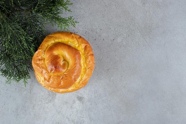 Pão saboroso e ramo de pinheiro dispostos na superfície de mármore