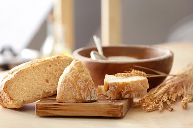 Pão saboroso, espigas de trigo e tábua de madeira na mesa da cozinha