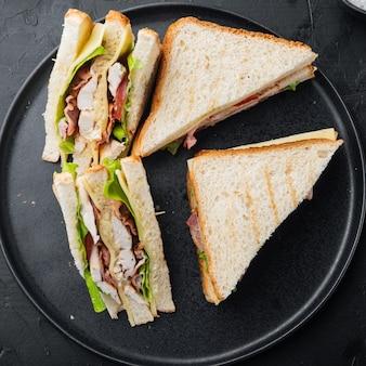 Pão sanduíche, tomate, alface e queijo amarelo, em fundo preto, vista superior