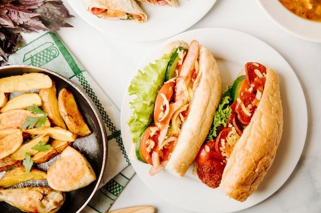 Pão sanduíches com alimentos misturados dentro e frango grelhado com batatas na panela.