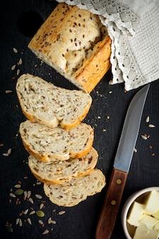 Pão saudável com farelo, sementes de girassol, abóbora, sementes de linho e gergelim em um velho fundo de madeira.