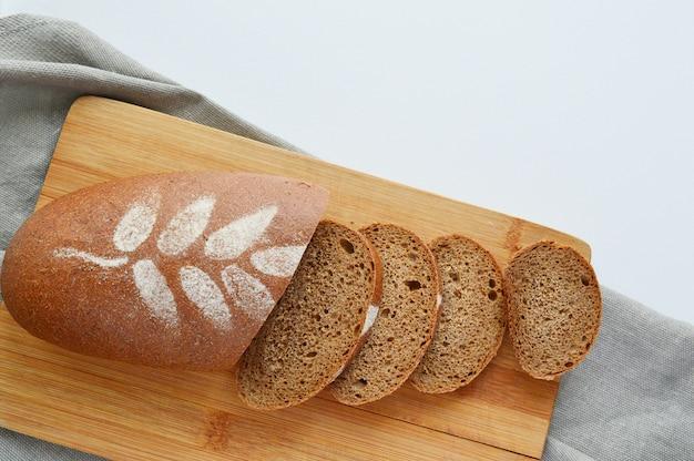 Pão saudável de centeio fatiado, espigas de trigo, com uma prancha de madeira velha em uma parede cinza, copie o espaço