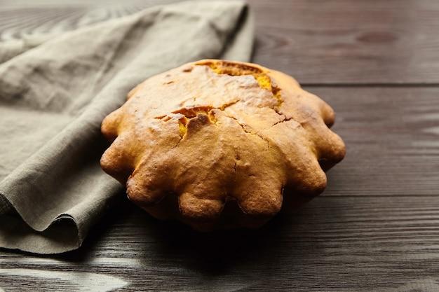 Pão sazonal de outono de abóbora em fundo escuro de madeira, pão de abóbora caseiro