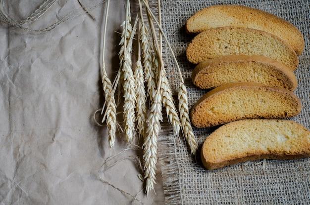 Pão seco branco rusk sobre tela e papel e espigas maduras de centeio