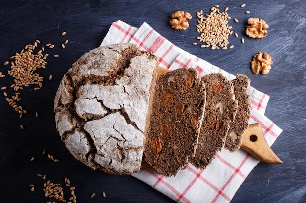 Pão sem fermento fatiado caseiro com grãos de centeio integral e trigo em madeira preta
