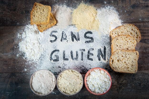 Pão sem glúten (sem glúten) e farinha no fundo de madeira