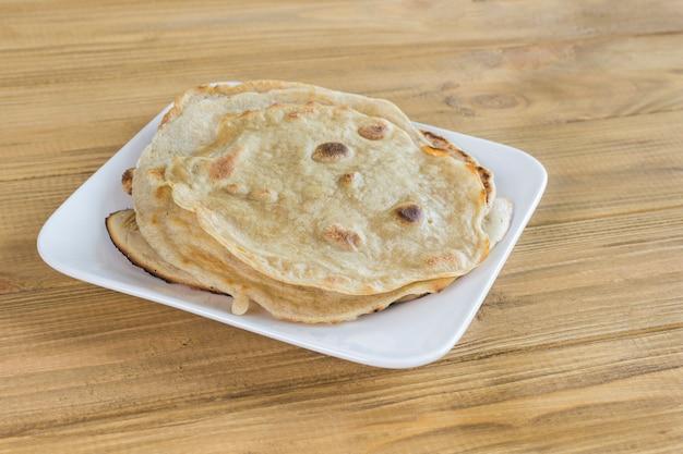Pão sírio em chapa branca sobre fundo claro de madeira.