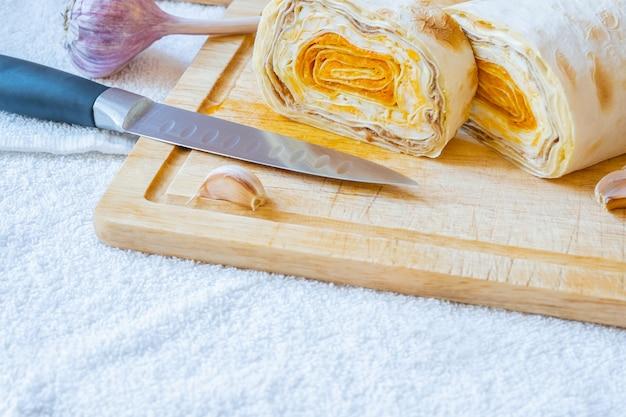 Pão sírio fatiado com recheio de cenoura em uma placa de madeira