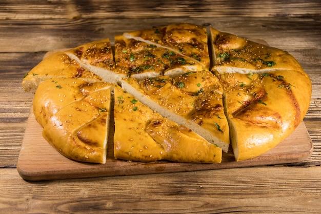 Pão sírio fatiado na tábua de cortar na mesa de madeira
