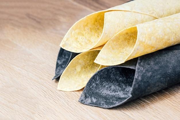 Pão sírio fino, branco e preto enrolado com um canudo