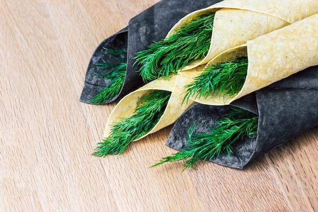 Pão sírio fino, branco e preto enrolado em um canudo com verduras