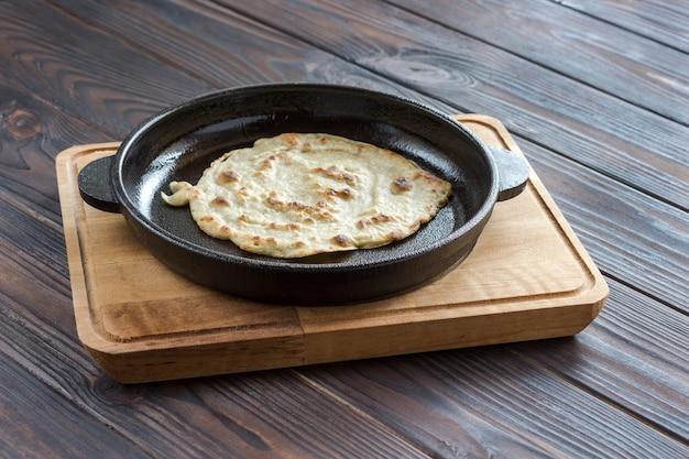 Pão sírio na frigideira no fundo escuro de madeira. comida natural. pão caseiro.