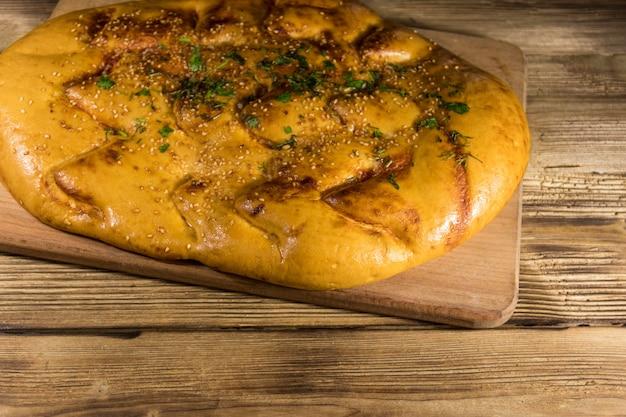 Pão sírio na tábua de cortar na mesa de madeira