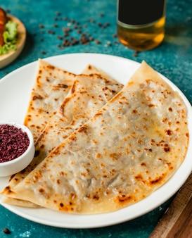 Pão sírio recheado com gutab do azerbaijão com carne picada, servido com sumagre