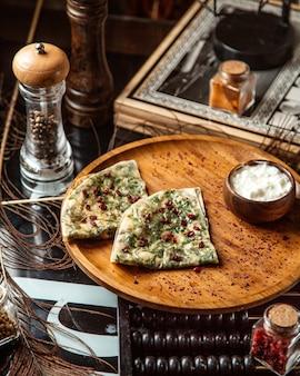 Pão sírio recheado com gutab do azerbaijão com ervas enfeitadas com sementes de romã e iogurte