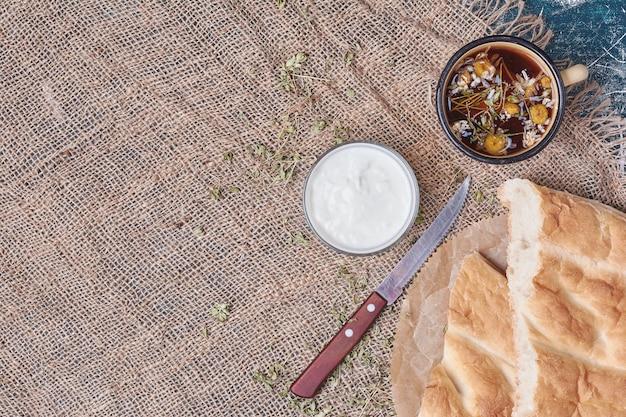 Pão tandir branco com iogurte e chá de ervas.