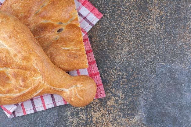 Pão tandoori meio fatiado em superfície de mármore