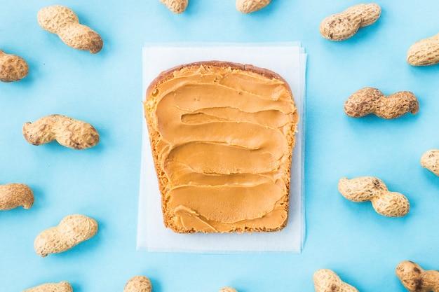 Pão torrada com pasta de noz entre amendoim em casca e sem sobre um fundo azul
